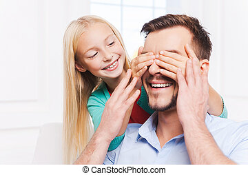 Guess who? Playful little girl covering eyes of her cheerful...