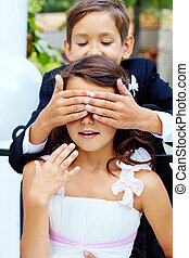 Guessing - Portrait of boy groom shutting eyes of his bride