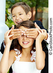 Guessing - Portrait of laughing boy groom shutting eyes of...