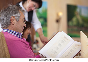 guest in restaurant reading the menu