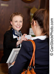 Guest receiving a business card at reception from a...