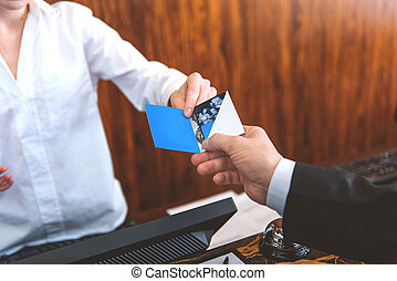 Guest taking room key card at check-in desk