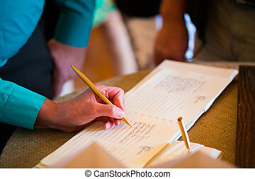 Person signing the guestbook at a wedding ceremony and reception.