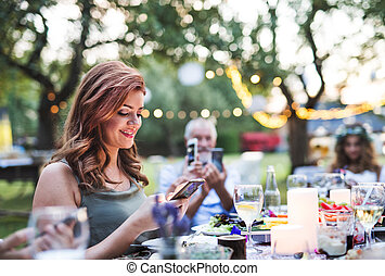 Guests with smartphones taking photo at wedding reception outside.