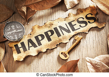 Guidance and key to happiness concept using printed word on burnt paper along with compass and golden key, surrounded by dry leaf