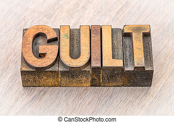guilt word abstract in wood type