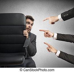 Guilty - Concept of businessman culprit behind a chair