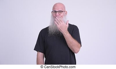 Guilty mature bald bearded man covering mouth - Studio shot...