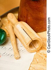 Guiro on wooden board and sheet with music - Vertical photo...