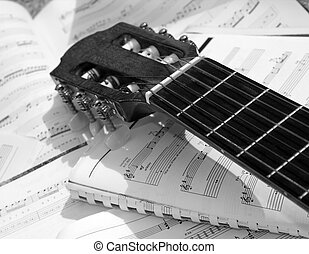 Acoustic guitar with sheet music in the background