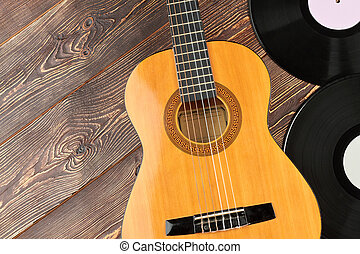 Guitar and vinyl records on wooden background.