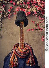 guitar dressed in a man's blue shirt with a scarf and a knitted cap next to a wall of flowers
