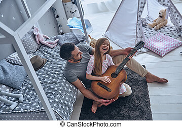Guitar fun. Top view of young father teaching his little...