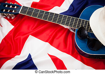 Guitar, hat and glasses on the background of the flag of Britain