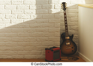 Guitar in brick room - White brick interior with guitar,...