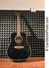 Guitar leans against a wall of soundproof foam