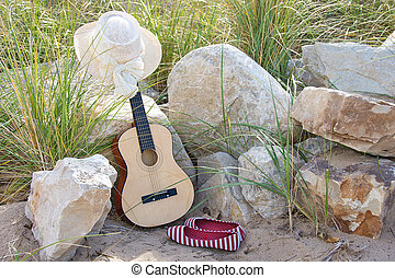 guitar on rocks with hat