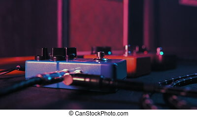 Guitar pedals and footswitch inside recording room. Close up of guitar pedals and musician's foot tapping on it for different sounds. 4k.