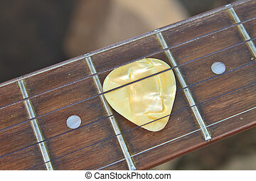 guitar pick on the fingerboard close up