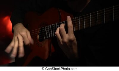 Guitar play a melody man. Close up. Light from behind -...