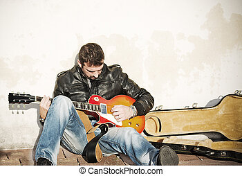 guitar player against the wall