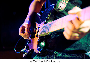 Close up image of guitar player on stage