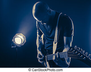 Guitar player in front of spotlight blue tone