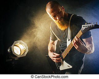 Guitar player in front of spotlight