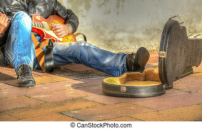 guitar player in the street with an open guitar case