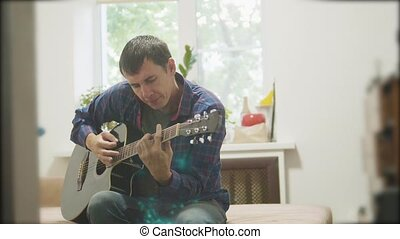 Guitar player playing and singing. man playing acoustic guitar slow motion video. in the room sits lifestyle on the couch. man and guitar concept
