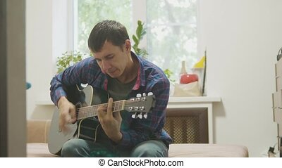 Guitar player playing and singing. man playing acoustic guitar slow motion video. in the room sits on the couch. man and lifestyle guitar concept