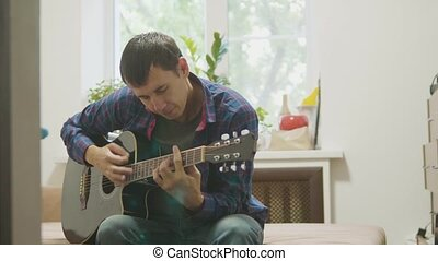 Guitar player playing and singing. man playing acoustic guitar slow motion video. in the room sits on the couch. man and guitar lifestyle concept