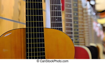 Guitar Shop. Lots of New Multicolored Acoustic Guitars are Hung in a Music Store Window. Acoustic guitars displayed in workshop. Guitars are sold in the Store. Shop musical instruments. 4K