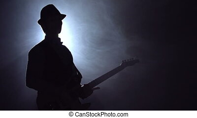Outline of man in hat playing guitar against the spotlight