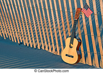 guitar with American flag on beach fence