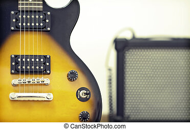 Guitar with amplifier in the background