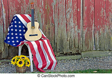 American flag with guitar and sunflower basket by old red barn.