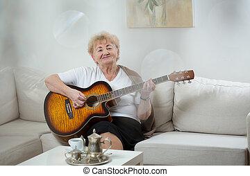 guitare, femme aînée, jouer