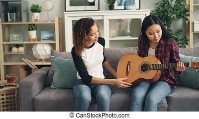 guitare, jeu, parler., elle, séance, sofa, african-american, jeune, gai, instrument, asiatique, tenue, enseignement, girl, home., musical, ami, femmes