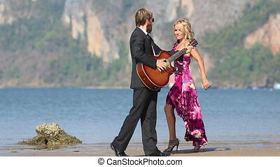 guitarist and blonde girl look at each other following around
