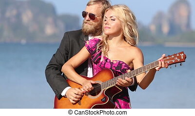guitarist and blonde girl  play guitar together and laugh