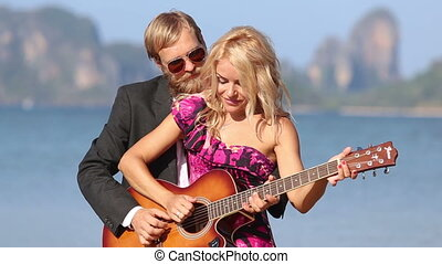 guitarist and girl hug play guitar together against cliffs