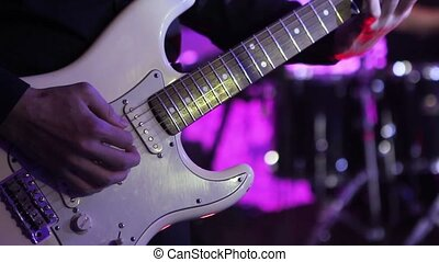 Guitarist at a live concert, a man plays the guitar, a live performance, he concert on stage, the musical group