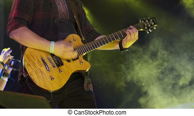 Guitarist at a Rock Concert Plays Electric Guitar on the Open Stage. Slow Motion