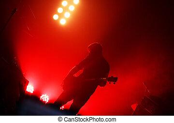guitarist at rock concert - Black silhouette of guitarist at...