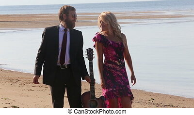 guitarist dances with blonde girl in red on beach
