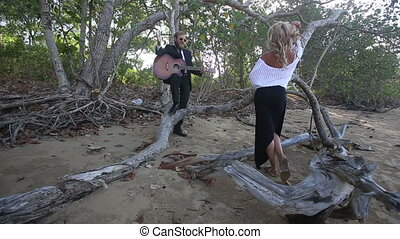 guitarist flirts with blonde girl she sits down on branch -...