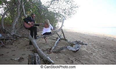 guitarist flirts with girl she sits down on branch and...