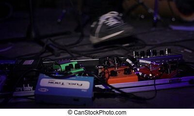 Guitarist foot pressing pedal board - Close-up of guitar...