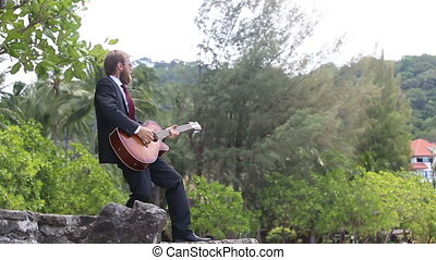 guitarist gesticulates against tropical trees
